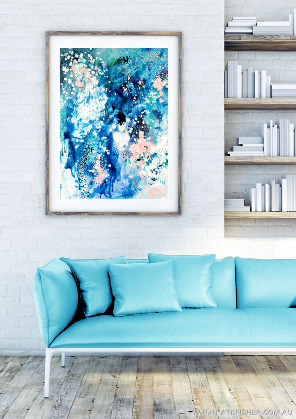 """""""When Snow Falls"""" abstract wall art print in blues and blush by Australian artist Kate Fisher styled in modern white living room interior with blue couch."""